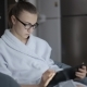 Girl in a Light Bathrobe. Sitting in a Chair and Enjoys the Tablet