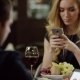 Couple Using Smartphone During Dating in Pompous Cafe
