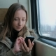 Pensive Woman Traveling on a Train and Using a Smartphone