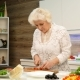 Mature Gray-haired Woman Cut the Cherry Tomatoes for a Salad in the Kitchen
