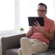 Man with Tablet Pc Sitting on Sofa at Home 8