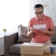 Man Reading Invoice and Opening Box at Home 15