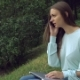 A Beautiful Girl Sitting in the Park and Talking on Thephone.