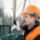 Worker Talking on the Radio, in the Hands Holding a Sledgehammer
