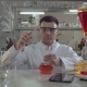 Handsome Professional Scientist Holding Flask in Lab