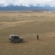 Aerial Scene, Jeep, Man Looks Horizon, Ancient Mounds, Steppe, Mountains