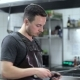 Professional Chef in a Commercial Kitchen in a Restaurant or Hotel Is Sharpening Knifes