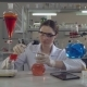 Attractive Professional Scientist Holding Flask in Lab