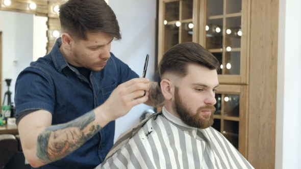 VideoHive Master Cuts Hair and Beard in the Barber Shop Black Gloves with Tattoos Off of Hands 19618321