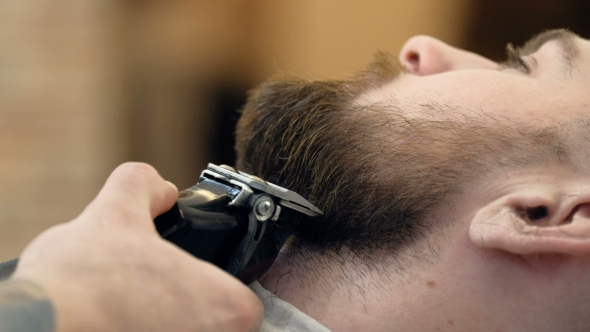 VideoHive Horizontal Portrait of a Barber Shaping Beard of His Client Using a Trimmer 19618409