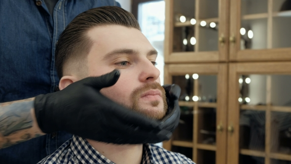 VideoHive Handsome Bearded Man While Getting Haircut By Hairdresser at the Barbershop 19620147