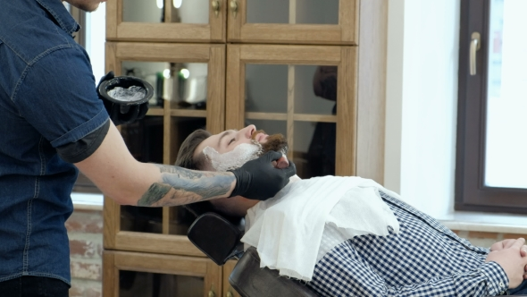 VideoHive Client During Beard Shaving in Barber Shop Barber Tattoo on His Arm 19620487