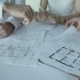 Hands of Three Workers Discussing Building Drawings in Office