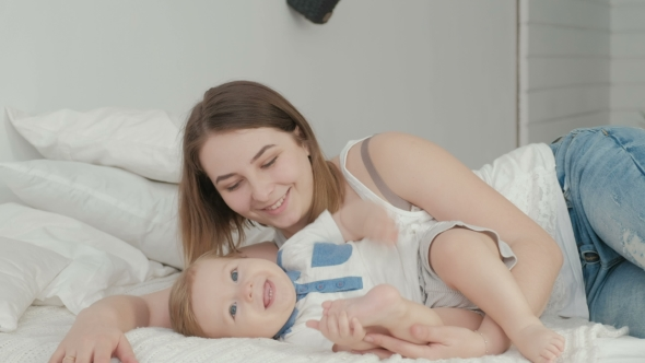 VideoHive Mother and Child on a White Bed Mom and Baby Boy in Diaper Playing in Sunny Bedroom 19622231