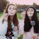 Hipster Girls Smiling and Laughing While Blowing Bubbles.