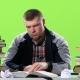 Man Sitting at His Desk Writes His Notes. Green Screen