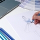 Designer with a Pencil Sketch Decorates Dresses in Blue.