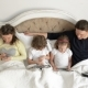 Family Is Using Mobile Devices Together in the Bedroom During Weekend at Home - VideoHive Item for Sale