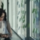 By the Window Stands a Woman with Glasses and Holding a Computer. - VideoHive Item for Sale