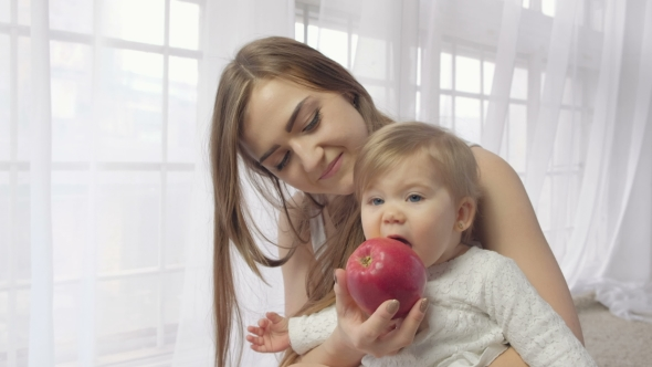 VideoHive Mother Holding Baby with Apple 19637076