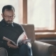 Stylish Man Reading a Book, Sitting in a Chair in a Stylish Office - VideoHive Item for Sale