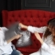 Two Happy Models Have Fight with Pillows on Red Sofa - VideoHive Item for Sale