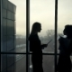 Dark Silhouettes of Two Women Against Window Inside Office - VideoHive Item for Sale