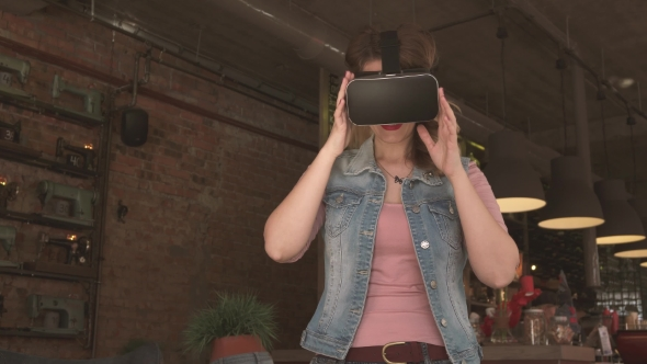 Woman Uses a Virtual Reality Glasses in Cafe
