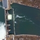 Opened Barriers on a City River. High Water in Spring. Aerial. Nulled