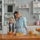 Beautiful Happy Mother with Orange Juice Child Boy in Kitchen Smiling, American Family Morning