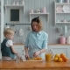 Healthy People - Little Boy and Young Mom Mother - Making Fresh Orange Juice in the Kitchen at