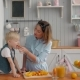 Happy Mother and Little Son Child Boy in the Kitchen, Happy Time and Togetherness, Mom Holding Fresh