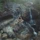 Aerial: Female Practising Meditation on Waterfall