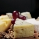 Cheese Platter with Nuts and Grapes on the Table
