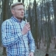 Handsome Elegant Man Smoking E-cigarette in the Forest in