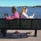 A Couple Sitting on a Bench on the Beach and Using Their Smartphones