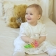 Little Girl in a White Dress Plays a Rattle - VideoHive Item for Sale