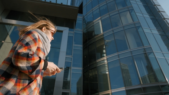 VideoHive Young Woman Walking in the Modern City Center with Her Smartphone in Hand 19717008