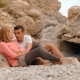 Young Couple Is Resting on the Rocks Near the Campfire - VideoHive Item for Sale