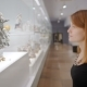 Young Woman in a Black Dress Looking at Flowers Made of Porcelain in Art Museum - VideoHive Item for Sale