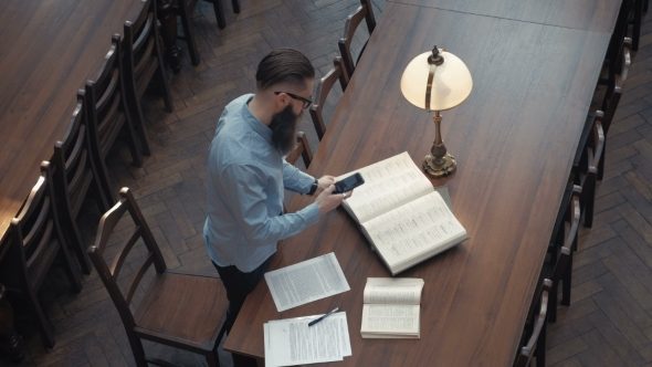 VideoHive Male Student with Open Book Working in a Library 19728432