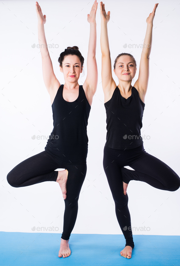 Two young women doing yoga asana tree pose Vrikshasana isolated on white background - Stock Photo - Images