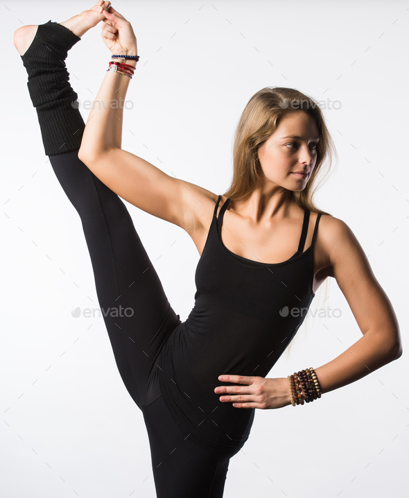 Smiling beutiful girl in black takes leg up. Isolated on white. - Stock Photo - Images