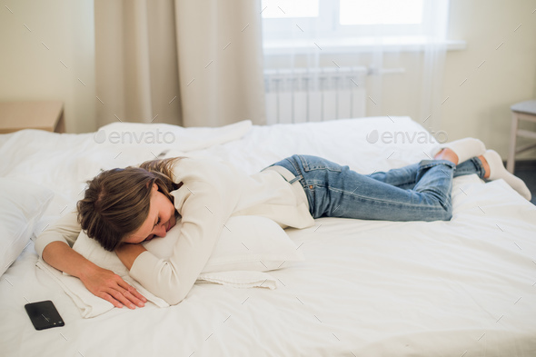 Relaxed young pretty woman sleeping in bed with blank screen mobile phone - Stock Photo - Images