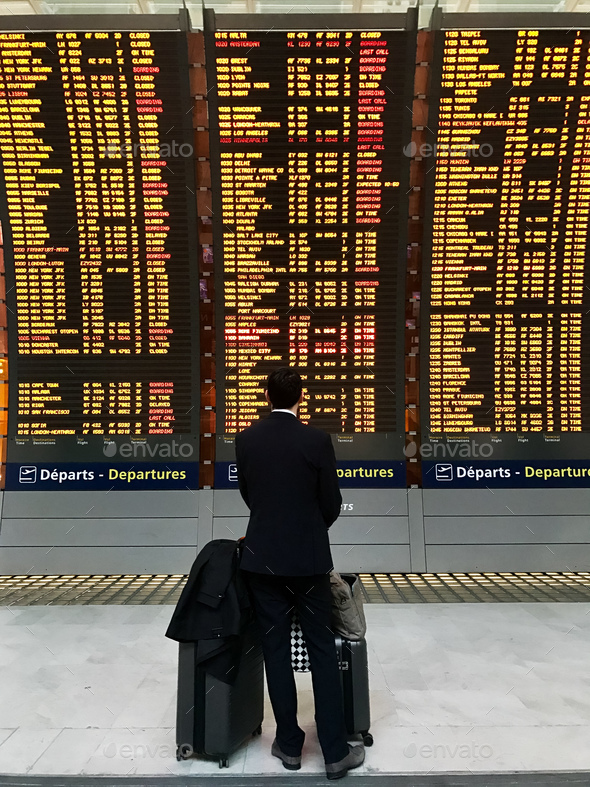 Businessman with a briefcase on a background of departure board at airport - Stock Photo - Images