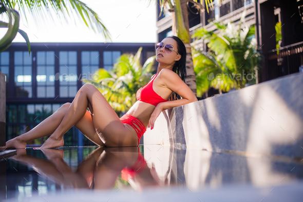 Woman sunbathing in bikini at tropical travel resort. Beautiful young woman lying near pool. - Stock Photo - Images