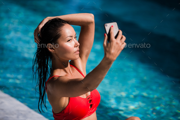 Beautiful woman in bikini taking a selfie by pool side on a sunny day at luxury hotel - Stock Photo - Images