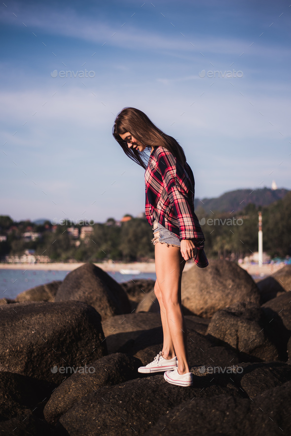 Sexy Girl in flannel shirt on the rocky beach. - Stock Photo - Images