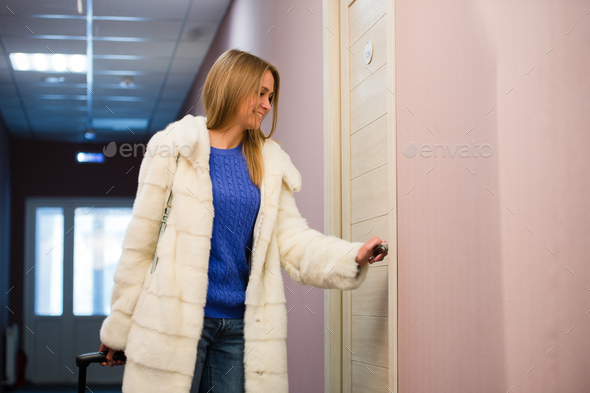 Young woman with plaid shirt and short jeans holding a suitcase and opening door of hotel room - Stock Photo - Images