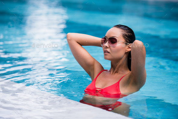 Woman wearing red swimsuit and sunglasses sitting in swimming pool, touching wet hair - Stock Photo - Images